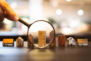 Hand holding magnifying glass and looking at house model, house